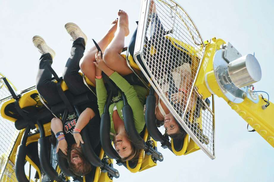 Caitlin Murray of Guilderland, 16, left, Jaimie Peck of Altamont, 17, center, and Ashley Aquilo of Guilderland, 16, ride upside down in the new Stinger ride on the opening day of the annual Altamont Fair on Tuesday Aug. 16, 2011 in Altamont, NY.  (Philip Kamrass / Times Union) Photo: Philip Kamrass / 00014132A