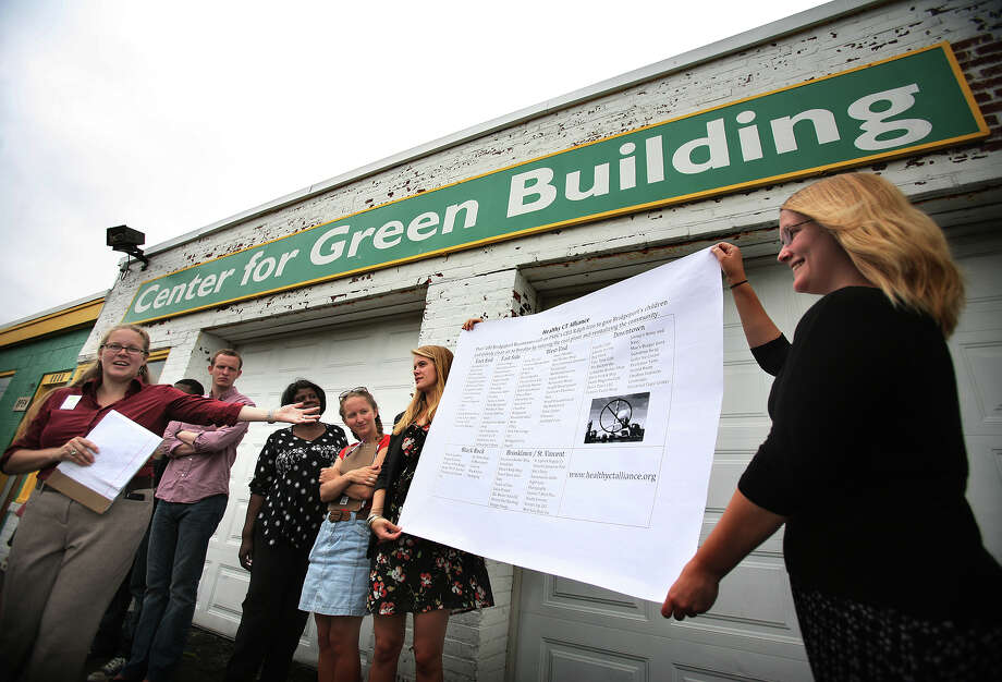 Claire Miller, left, community organizer for Toxics Action Center, unveils a list of local businesses that have endorsed a campaign to retire the Bridgeport Harbor station coal burning power plant, at the Center for Green Building on Fairfield Avenue in Bridgeport on Wednesday, August 15, 2012. Photo: Brian A. Pounds / Connecticut Post