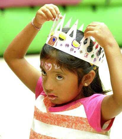 Michelle Pani, 6, of Danbury, tries on the magic color scrach crown she crafted during Danbury Kidz Camp at the Danbury Fair mall Tuesday, Aug. 14, 2012. Photo: Michael Duffy
