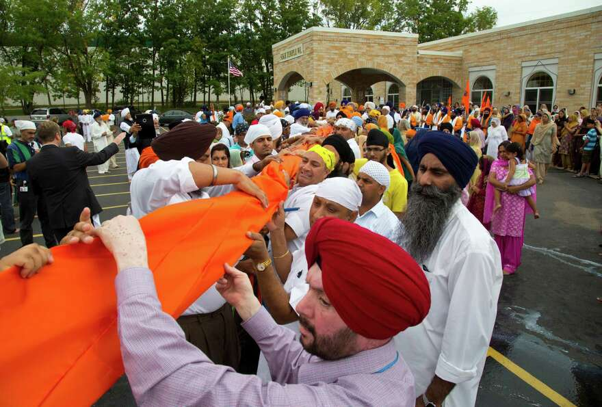 People attend a flag ceremony being held outside the Sikh Temple of Wisconsin in Oak Creek, Wis., Su