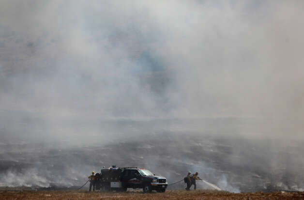 Firefighters work on a brush fire on Bettas Road on Wednesday, August 15, 2012. The Taylor Bridge Fire has forced hundreds to evacuate and has burned dozens of homes. Photo: JOSHUA TRUJILLO / SEATTLEPI.COM