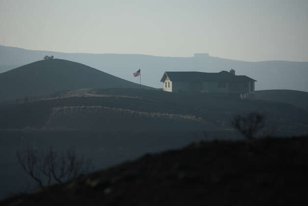 A home is shown still standing among scorched hillsides on Wednesday, August 15, 2012 along Highway 10 near Ellensburg. The Taylor Bridge Fire has forced hundreds to evacuate and has burned dozens of homes. Photo: JOSHUA TRUJILLO / SEATTLEPI.COM