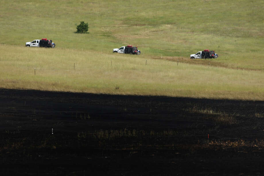 Firefighters head up a hill to attack a fire from the ground on Wednesday, August 15, 2012 along Highway 97. Photo: JOSHUA TRUJILLO / SEATTLEPI.COM