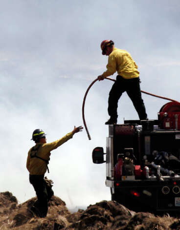 Firefighters pull a hose into position to quench a smoldering field Wednesday near Cle Elum.(AP Photo/Elaine Thompson) Photo: Associated Press