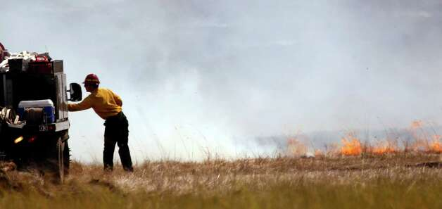 Flames in a smoldering field inch toward a firefighter Wednesday, near Cle Elum.  (AP Photo/Elaine Thompson) Photo: Associated Press