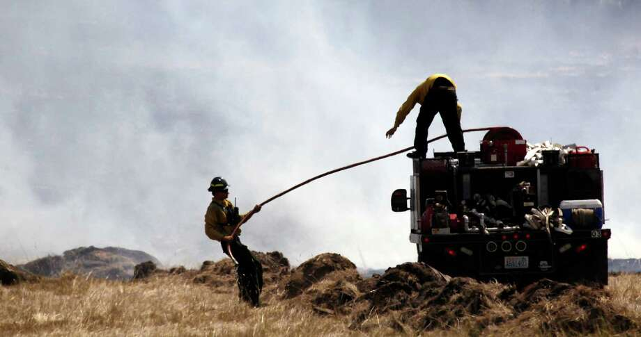 Firefighters pull a hose into position to quench a smoldering field Wednesday, near Cle Elum.(AP Photo/Elaine Thompson) Photo: Associated Press