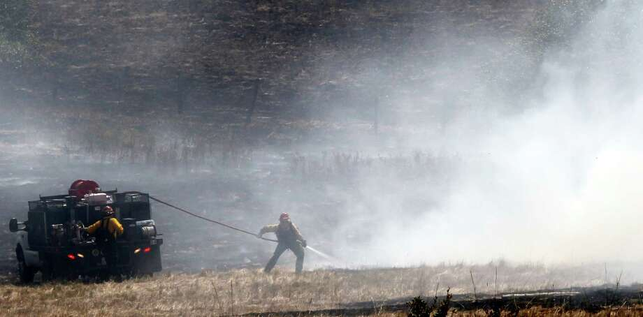 A firefighter pulls a hose toward a hot spot left from a wildfire Wednesday near Cle Elum.  (AP Photo/Elaine Thompson) Photo: Associated Press