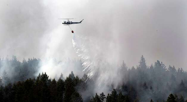 A helicopter drops water on a blaze Wednesday near Cle Elum,. (AP Photo/Elaine Thompson) Photo: Associated Press