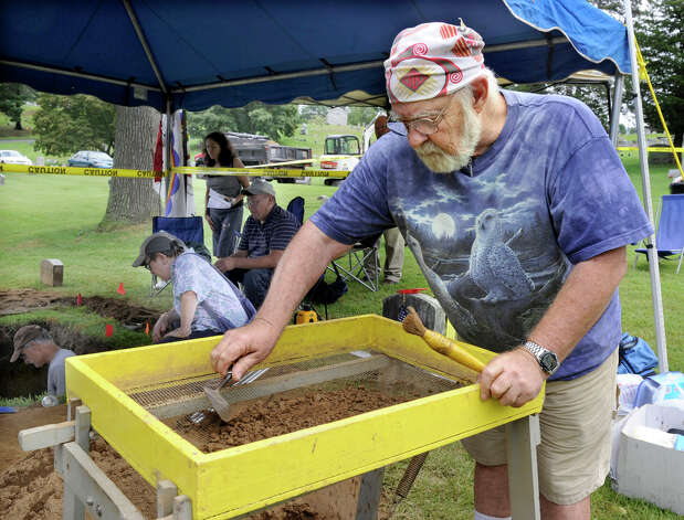 Ken Batrice, of East Haddam, Ct. screens dirt that was dug from the gravesite of Albert Afraid of Hawk at Wooster Cemetary Wednesday, Aug. 15, 2012. The dirt is screened to look for any artifacts that might be mixed in with the dirt, such as buttons or glass beads. Photo: Carol Kaliff