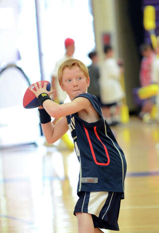 Jason Carroll, 10, of Stamford, tosses around a football during Peak Performance All Sports Camp at Westhill High School in Stamford on Wednesday, Aug. 15, 2012. The camp offers a combination of traditional sports games, physical education activities, and cooperative games for boys and girls ages 4-12. Photo: Amy Mortensen / Connecticut Post Freelance