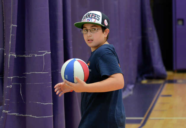 Nicholas Otis, 11, of Stamford, grabs a basketball during Peak Performance All Sports Camp at Westhill High School in Stamford on Wednesday, Aug. 15, 2012. The camp offers a combination of traditional sports games, physical education activities, and cooperative games for boys and girls ages 4-12. Photo: Amy Mortensen / Connecticut Post Freelance