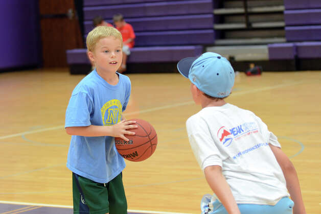 Colin Lenskood, 8, of Norwalk, plays basketball with Jack Palmer, 10, of Stamford, during Peak Performance All Sports Camp at Westhill High School in Stamford on Wednesday, Aug. 15, 2012. The camp offers a combination of traditional sports games, physical education activities, and cooperative games for boys and girls ages 4-12. Photo: Amy Mortensen / Connecticut Post Freelance