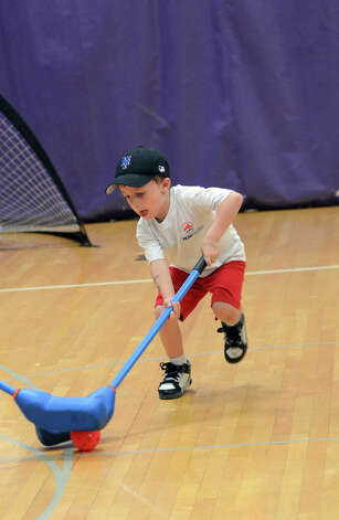 CJ Berlingo, 5, of Stamford, goes for a block while playing floor hockey during Peak Performance All Sports Camp at Westhill High School in Stamford on Wednesday, Aug. 15, 2012. The camp offers a combination of traditional sports games, physical education activities, and cooperative games for boys and girls ages 4-12. Photo: Amy Mortensen / Connecticut Post Freelance