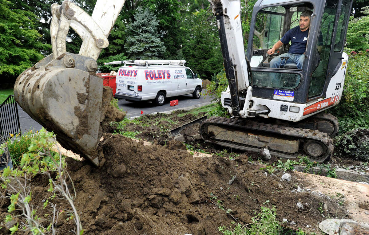 Firmino Machado of New Milford, an employee of Foley's Pump Service of Danbury, digs a trench for a waterline at a home in Redding, Wednesday, Aug. 15, 2012.
