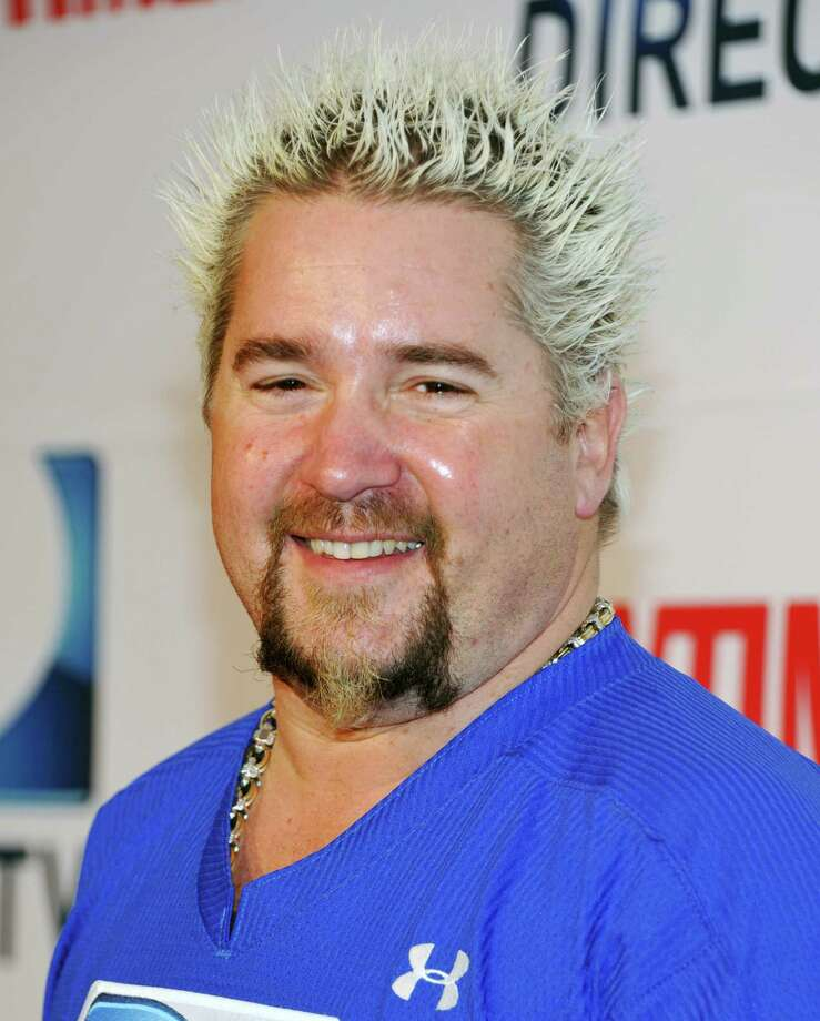 """FILE - In this Feb. 5, 2011 file photo, celebrity chef and TV host Guy Fieri participates in DirecTV's Fifth Annual Celebrity Beach Bowl in Dallas, Texas. Police say a thief using climbing gear rappelled into a San Francisco exotic car dealership and stole television celebrity chef Guy Fieri's $200,000-plus Lamborghini sports car.  The bright yellow Gallardo owned by the star of the Food Network's """"Diners, Drive-ins and Dives"""" was taken Tuesday, March 8, 2011. (AP Photo/Evan Agostini, file) Photo: Evan Agostini / AGOEV"""