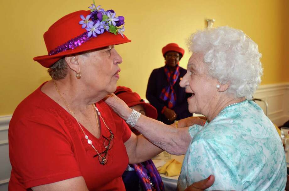 Gladys Platero, left, a member of the Bridgeport Red Hat Society greets her friend Mary Mazur, who turned 100 today, as she enters a luncheon in her honor held at TestoâÄôs Restaurant in Bridgeport, Conn. on Wednesday, Aug. 15, 2012.  City resident Mary Mazur turned 100 today and was surprised by a crowd of family and friends at a congratulatory luncheon in her honor. Photo: Contributed Photo/Wayne Ratzenbe, Wayne Ratzenberger/Contributed P / Connecticut Post Contributed Wayne Ratzenberger