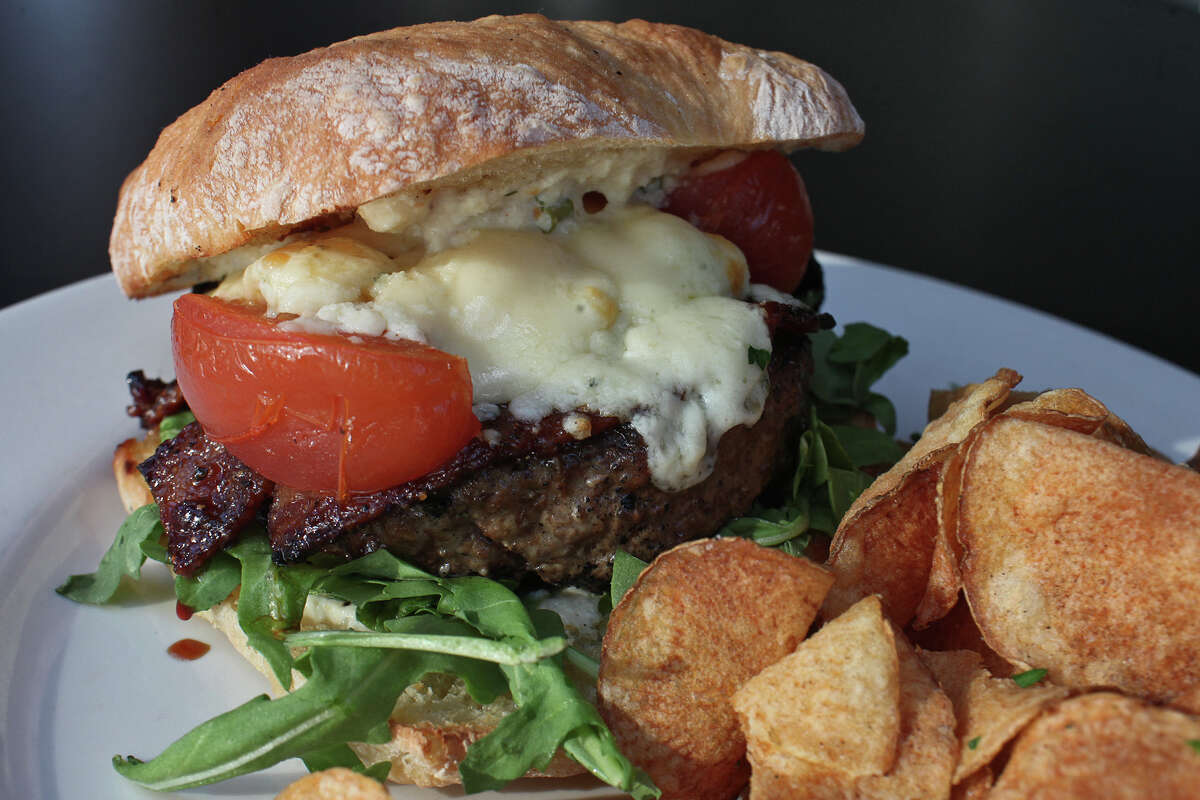 The burger at Knife & Fork Gastropub is made with chuck & short rib beef, tomato confit, candied bacon, gorgonzola, horseradish cream and arugula served on ciabatta.