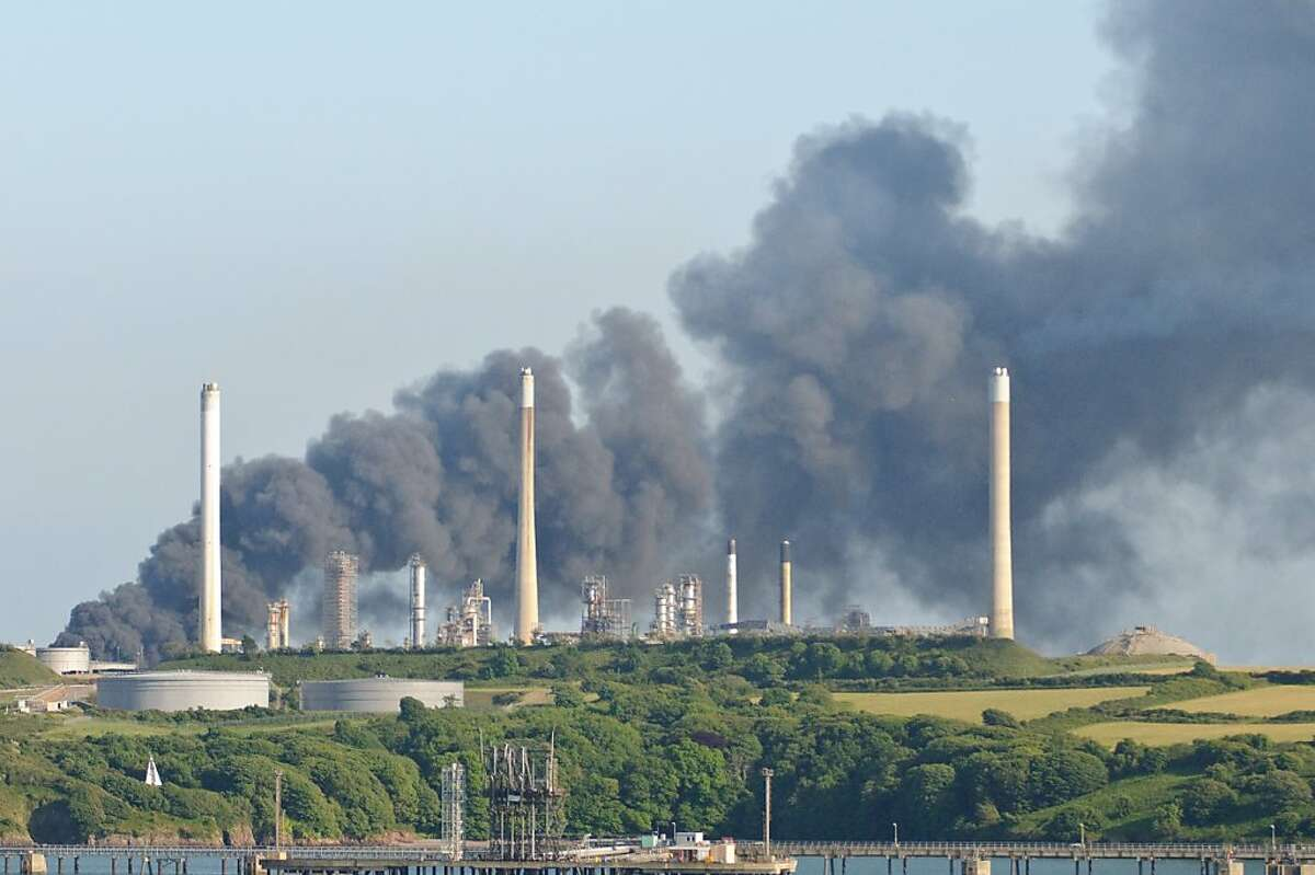 Thick black smoke rises from Chevron's Pembroke refinery in Wales where four workers were killed.