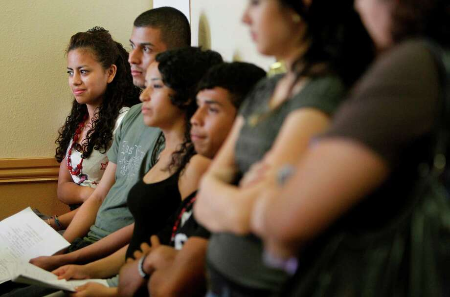 Gabriela Fajardo, 15, smiles as she waits next in line to process her passport at the Honduran Consulate and apply for relief under a new Obama Administration policy that suspends deportation for immigrants brought to the country at a young age on Wednesday, Aug. 15, 2012, in Houston. Fajardo has been waiting since yesterday morning at 11 a.m. outside the consulate to receive a passport. No passport are required to apply, but applicants are still waiting inline for days to receive a passport. Consulate employees  have processed 153 since Monday through early Wednesday afternoon. Photo: Mayra Beltran, Houston Chronicle / © 2012 Houston Chronicle