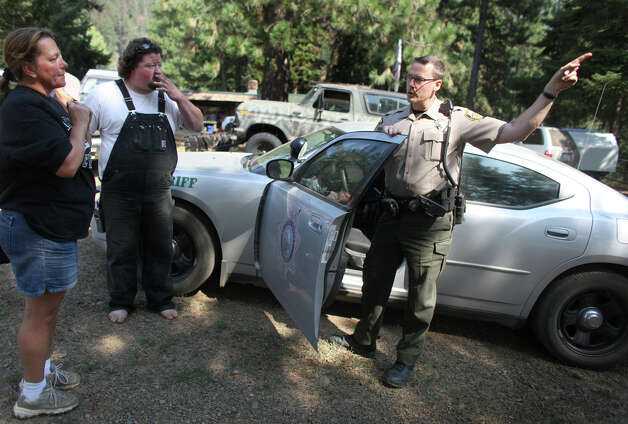 Kittitas County Sheriff's Deputy Chris Whitsett informs Carla Sweet and Matt Brink to prepare to evacuate their homes on Wednesday, August 15, 2012 near Lauderdale Junction. The Taylor Bridge Fire has forced hundreds to evacuate and has burned dozens of homes. Photo: JOSHUA TRUJILLO / SEATTLEPI.COM