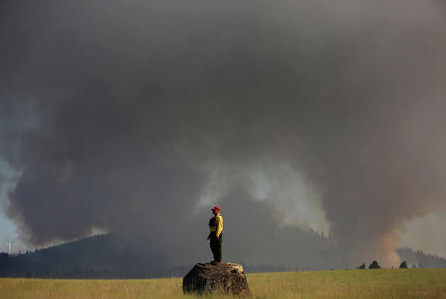 Marcus Johns with the Department of Natural Resources, watches as the Taylor Bridge Fire burns on the south side of Highway 970 near Swauk Prairi
