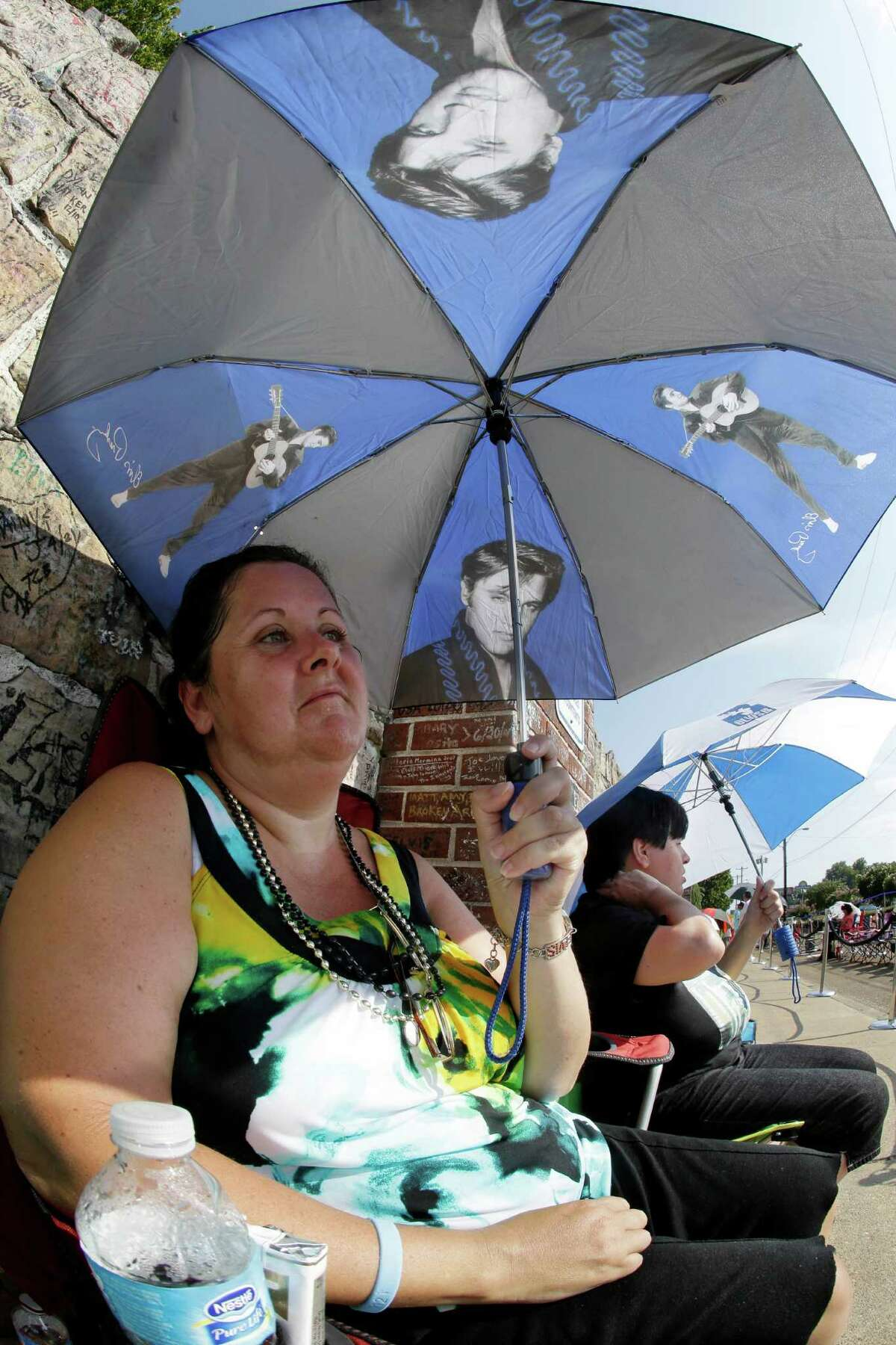 Elvis Presley fan Mary Ann Seiber, from Knoxville, Tenn., waits in line outside Graceland, Presley's Memphis, Tenn. home, on Wednesday, Aug. 15, 2012. Fans are lined up to take part in the annual candlelight vigil marking the 35th anniversary of Presley's death.