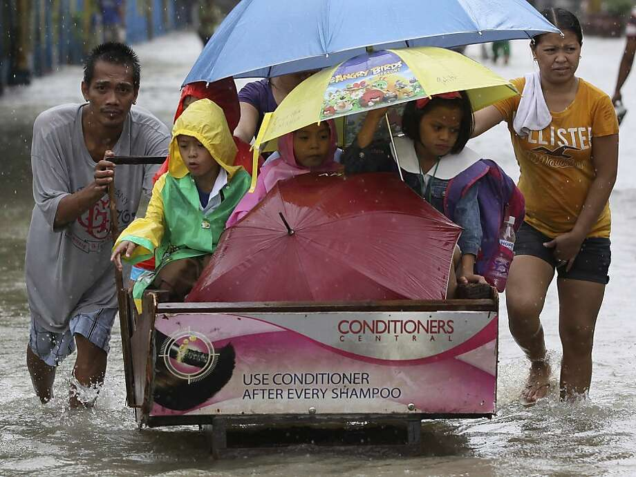 A man pushes a cart full of schoolchildren as they cross a flooded road in suburban Pasig, east of Manila, Philippines, Wednesday Aug. 15, 2012. A second tropical storm in as many weeks battered the northern Philippines on Wednesday as forecasters warned that the still-reeling capital could see more flooding.  Photo: Aaron Favila, Associated Press