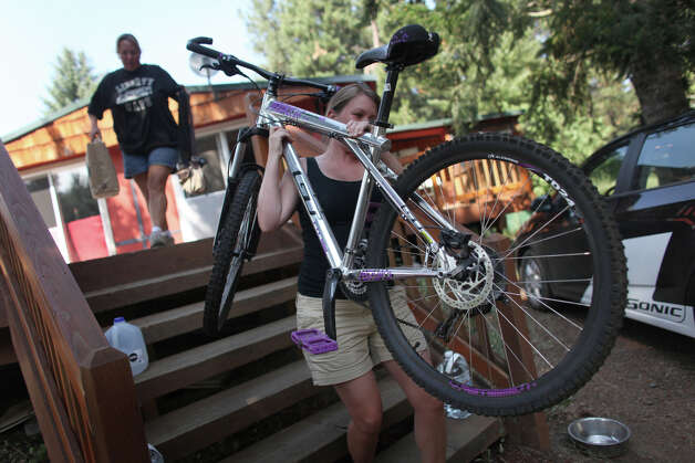 Pandora Bjeletich packs up a bicycle as she helps a friend prepare to evacuate near Lauderdale Junction on Wednesday, August 15, 2012. The Taylor Bridge Fire has forced hundreds to evacuate and has burned dozens of homes. Photo: JOSHUA TRUJILLO / SEATTLEPI.COM