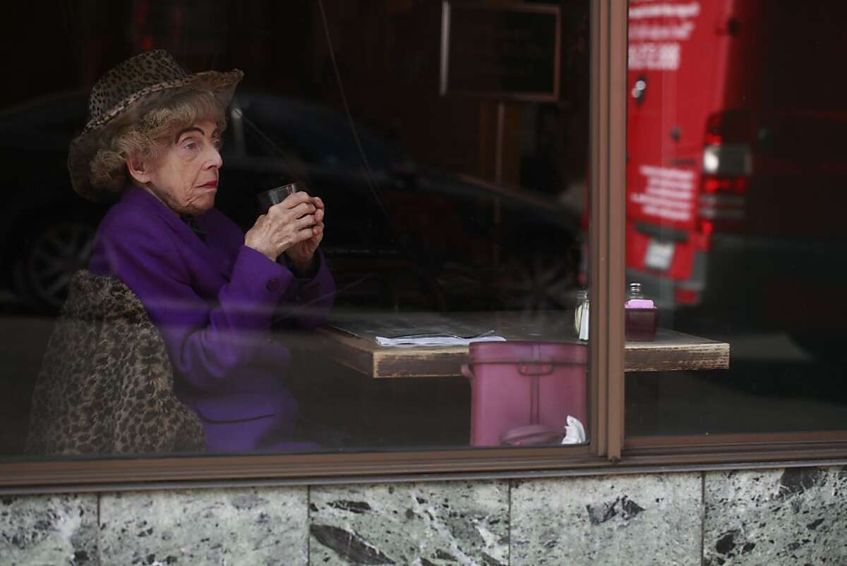 Dining alone, one half of the famed San Francisco twins, Marian Brown, 85, looks out the window Uncle Vito's Pizza on Wednesday Aug, 15, 2012 in San Francisco, Calif where she and her sister Vivian have frequented for years. Vivian Brown has fallen ill and has been in the hospital for the past month.