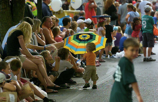 A young child holds an umbrella as rain falls during a parade down Third Street which was held to kick off the 2012 Little League World Series in Williamsport, Penn. on Wednesday August 15, 2012. Photo: Christian Abraham / Connecticut Post