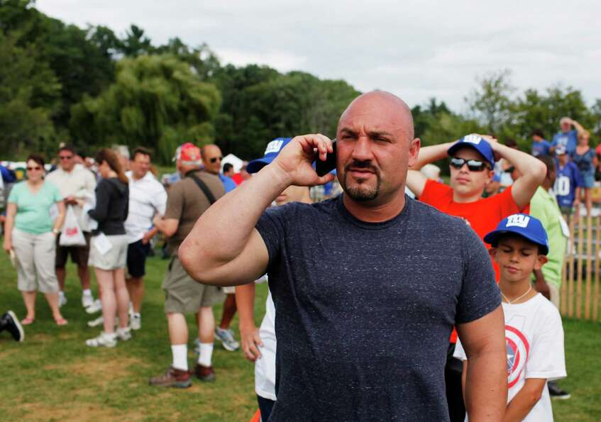 Jay Glazer talks on the phone on the sidelines of New York Giants preseason training camp at UAlbany