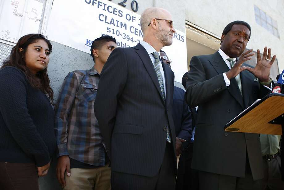 Attorneys Patrick Goggin (middle) and John Burris (right), with their staff (behind) announce filing the first lawsuit against Chevron Corp. over the refinery fire in Richmond. Photo: The Chronicle