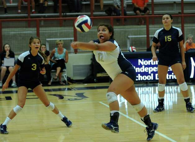 Alex Guerrero of O'Connor strains to reach the ball during high school volleyball against Reagan at O'Connor High School on Wednesday, Aug. 15, 2012. Teammates Emily Starnes, left, and Brianna Sotello, right, watch. Photo: Billy Calzada, San Antonio Express-News / © San Antonio Express-News