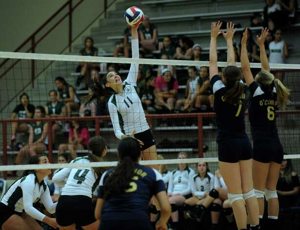 Ashlie Reasor of Reagan (11) spikes the ball as Laura Fox (7) and Brooke Burgess (6) of O'Connor attempt to defend during high school volleyball action at O'Connor High School on Wednesday, Aug. 15, 2012. Photo: Billy Calzada, San Antonio Express-News / © San Antonio Express-News