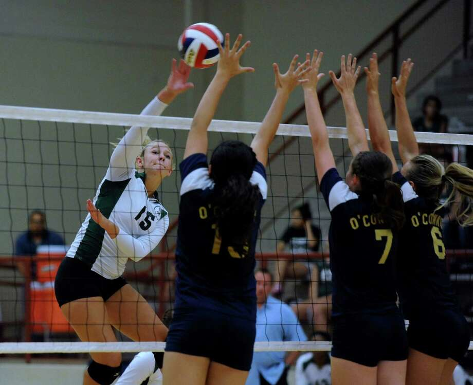Brooke Sassin of Reagan (15) tips the ball over Brianna Sotello (15), Laura Fox (7), and Brooke Burgess (6) of O'Connor during high school volleyball action at O'Connor High School on Wednesday, Aug. 15, 2012. Photo: Billy Calzada, San Antonio Express-News / © San Antonio Express-News