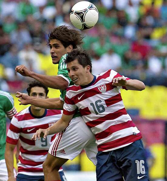 Manuel Viniegra, left, of Mexico jumps for the ball with Francisco Torres of USA.