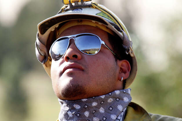 Firefighter Hector Gonzalez looks up at a fire as he prepares to work on a fire line Wednesday, Aug. 15, 2012, near Cle Elum, Wash. Crews fighting the large blaze in central Washington hope to increase containment levels by Wednesday evening, but are keeping a wary eye on weather conditions later in the week. The fire burning near Cle Elum has burned dozens of homes and caused about 900 people to evacuate. Photo: Elaine Thompson / Associated Press