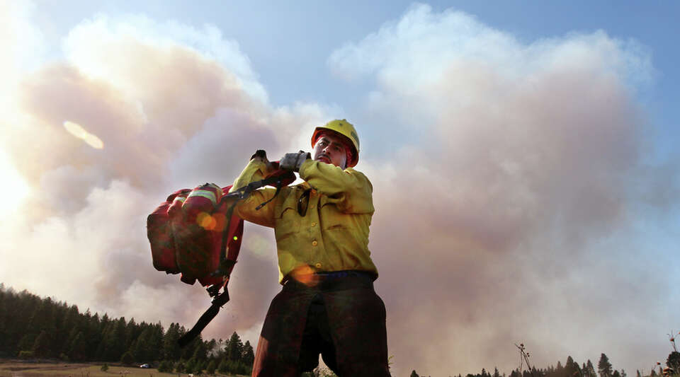 As smoke rises behind, firefighter Jose Barajas hefts his pack as he gets his equipment ready Wednes
