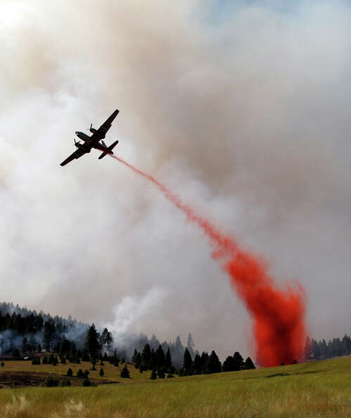 A plane drops fire retardant on a hillside in Horse Canyon Wednesday, Aug. 15, 2012, near Cle Elum,