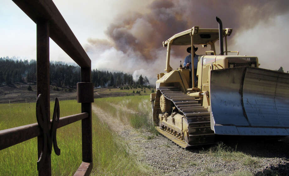 Brian Stickney moves a bulldozer at a friend's ranch as a cloud of smoke rises behind Wednesday, Aug. 15, 2012, near Cle Elum, Wash. Crews fighting the large blaze in central Washington hope to increase containment levels by Wednesday evening, but are keeping a wary eye on weather conditions later in the week. The fire burning near Cle Elum has burned dozens of homes and caused about 900 people to evacuate. (AP Photo/Shannon Dininny) Photo: Elaine Thompson / Associated Press