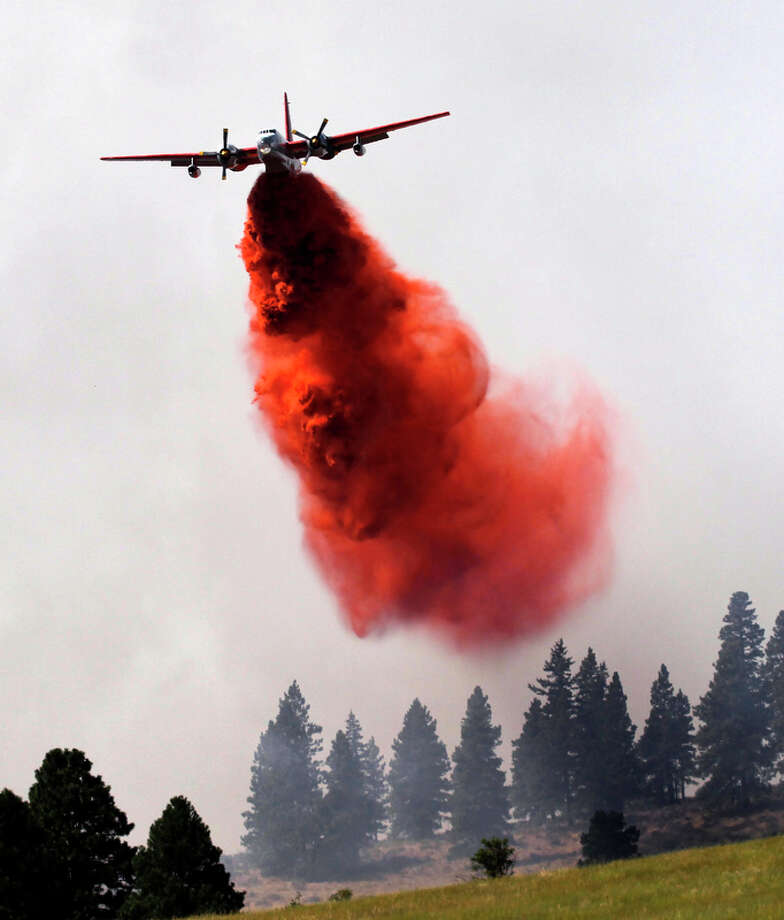 A plane drops fire retardant on a hillside in Horse Canyon Wednesday, Aug. 15, 2012, near Cle Elum, Wash. Crews fighting the large blaze in central Washington hope to increase containment levels by Wednesday evening, but are keeping a wary eye on weather conditions later in the week. The fire burning near Cle Elum has burned dozens of homes and caused about 900 people to evacuate. Photo: Elaine Thompson / Associated Press