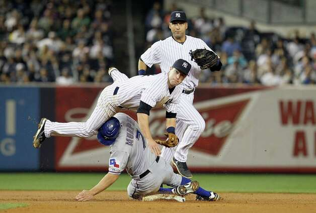 NEW YORK, NY - AUGUST 15:  Jayson Nix #17 of the New York Yankees falls over David Murphy #7 of the Texas Rangers as he completes a double play to end the fourth inning as teammate Derek Jeter #2 looks on at Yankee Stadium on August 15, 2012  in the Bronx borough of New York City.  (Photo by Jim McIsaac/Getty Images) ***BESTPIX*** Photo: Jim McIsaac, Getty Images / 2012 Getty Images