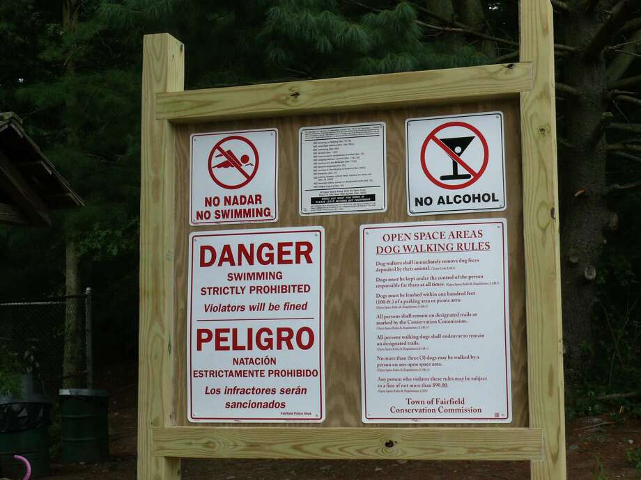 New signs have been installed at the entrances to the Lake Mohegan open space informing visitors swimming is not only not allowed, but is dangerous. Photo: Genevieve Reilly / Fairfield Citizen