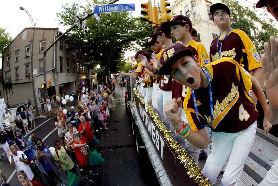 Members of the 2012 McAllister Park All-Stars ride in the Little League Grand Slam Parade as it makes its way through downtown Williamsport, Pa., Wednesday, Aug. 15, 2012. The Little League World Series tournament begins Thursday in South Williamsport, Pa. (Gene J. Puskar / Associated Press)