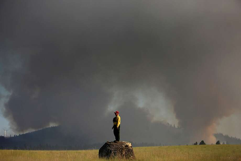 Marcus Johns with the Department of Natural Resources, watches as the Taylor Bridge Fire burns on the south side of Highway 970 near Swauk Prairie Road on Wednesday, Aug. 15, 2012 near Cle Elum, Wash. The Taylor Bridge Fire has forced hundreds to evacuate and has burned dozens of homes. (AP Photo/seattlepi.com, Joshua Trujillo) Photo: Joshua Trujillo, Associated Press