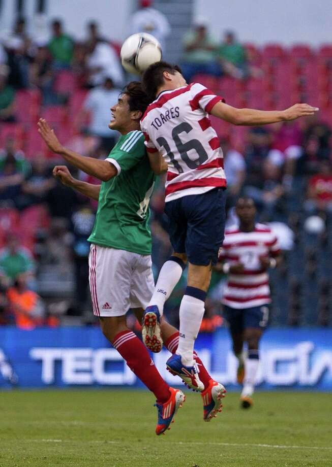 Mexico's Manuel Vinegra, left, and U.S. Edgar Castillo go for a header during a friendly soccer match in Mexico City, Wednesday, Aug. 15, 2012. (AP Photo/Christian Palma) Photo: Christian Palma, Associated Press / AP