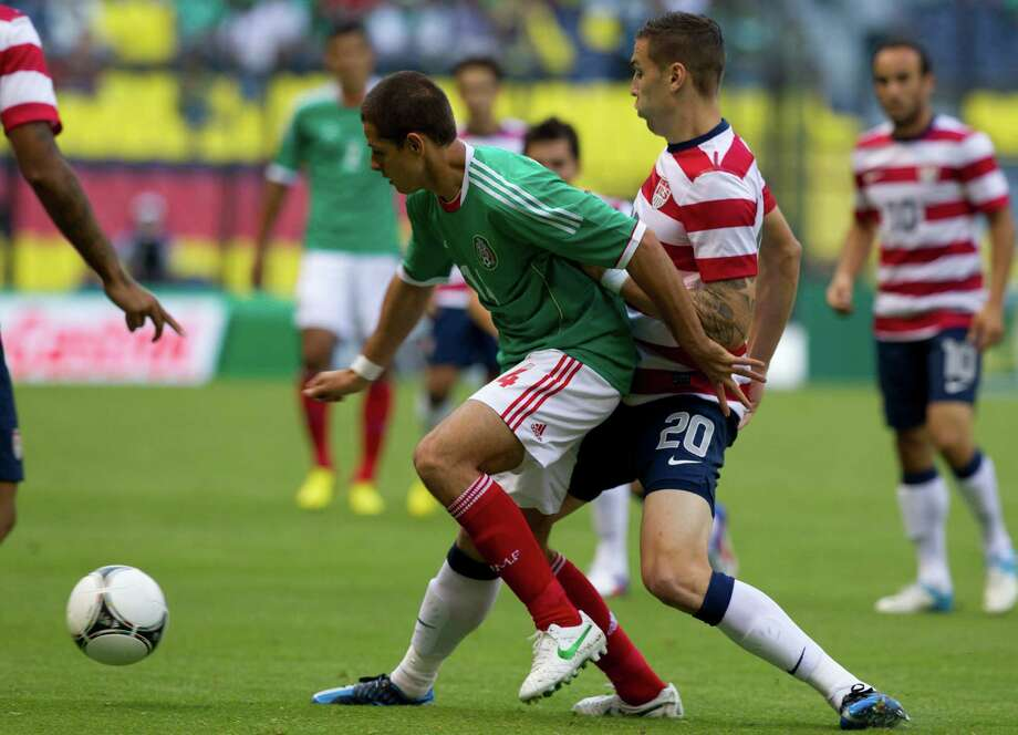 Mexico's Javier Hernandez, left, and U.S. Geoff Cameron battle for the ball during a friendly soccer match in Mexico City, Wednesday, Aug. 15, 2012. (AP Photo/Eduardo Verdugo) Photo: Eduardo Verdugo, Associated Press / AP