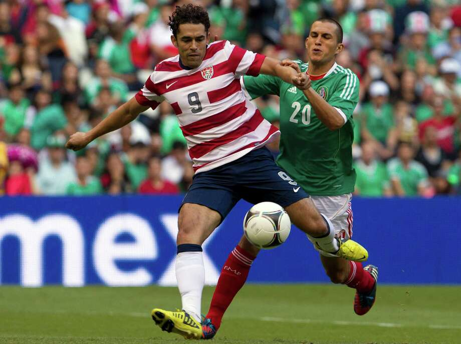 Mexico's Jorge Torres, back, challenges U.S. Danny Williams during a friendly soccer match in Mexico City, Wednesday, Aug. 15, 2012. (AP Photo/Christian Palma) Photo: Christian Palma, Associated Press / AP