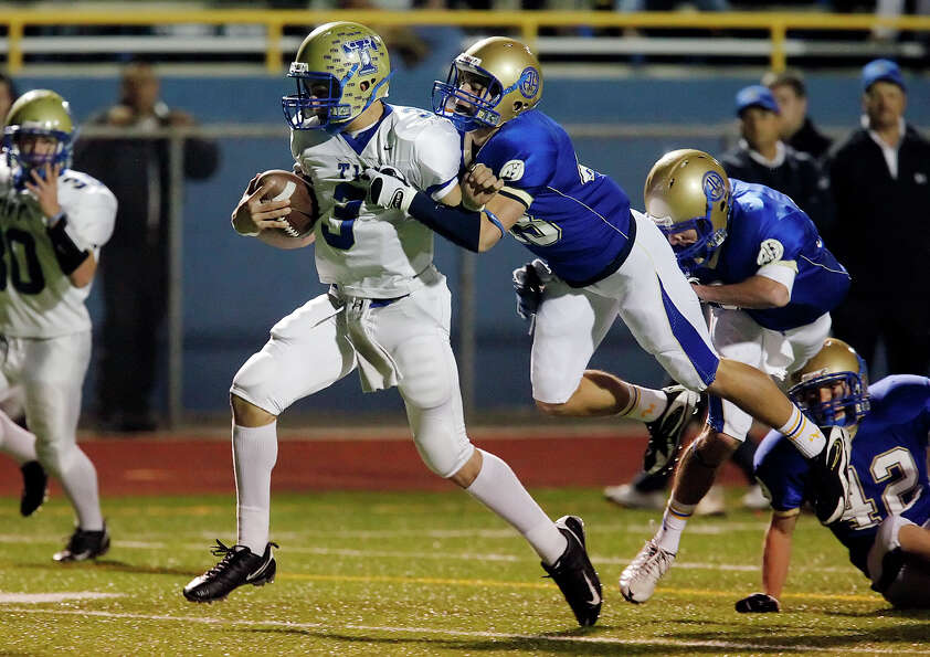 Kerrville-Tivy's Johnny Manziel (03) gets Alamo Heights' Philip Massari (43) off his feet at Orem