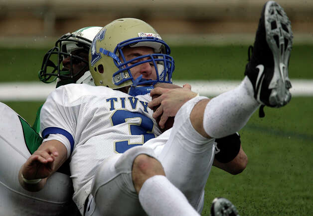 Kerrville-Tivy's Johnny Manziel (right) gets hauled down by Brenham's Blake Sander during the 4A football state semifinals in Georgetown, Texas on Saturday, Dec. 12, 2009. Tivy lost 31-21. Photo: Kin Man Hui, San Antonio Express-News / kmhui@express-news.net